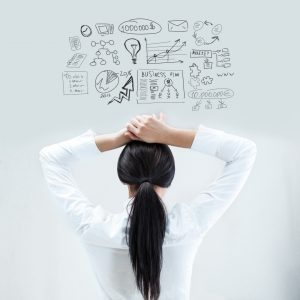 Rear view of young business woman thinking of her plans with hands behind head